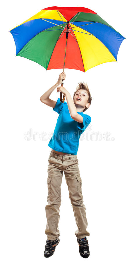 Beautiful funny boy in t-shirt flying with a multicolored umbrella. Beautiful funny boy boy in red t-shirt holding a multicolored umbrella flying carried by the royalty free stock images