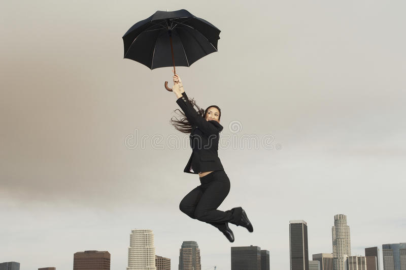 Businesswoman With An Umbrella Flying Above City. Full length of young businesswoman with an umbrella flying above city stock photos