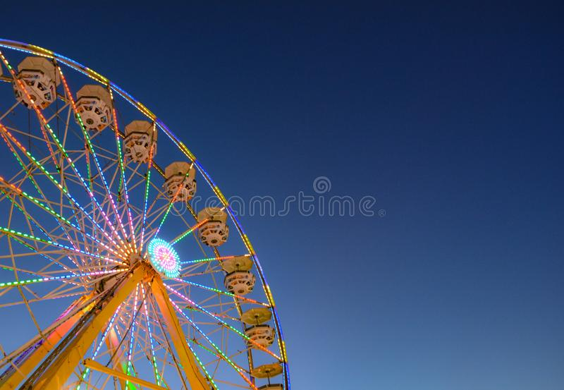 Ferris Wheel at State Fair. Ferris wheel all lit up at sundown with copy space provided on right side of image. Unusual ferris wheel round seats with umbrella stock photos