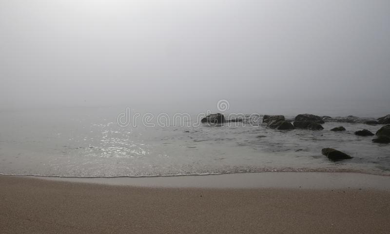Fog in el arenal beach in mallorca. Rare and unusual heavy fog over the coast with sun umbrellas and shoreline with rocks at El Arenal beach touristic area royalty free stock images
