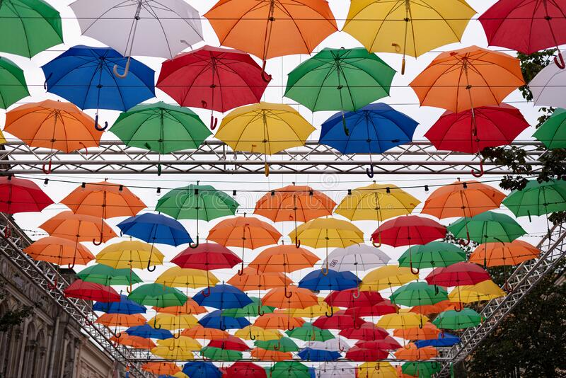 Funny multi-colored decorative umbrellas in the sky decorating a tourist street in St. Petersburg. Unusual street decorations royalty free stock images