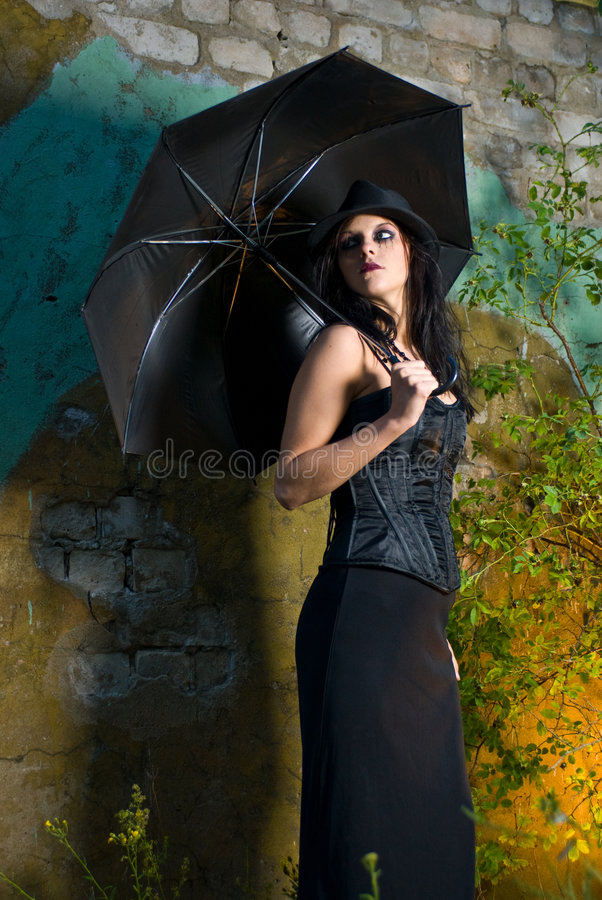 Goth Girl With Umbrella. Goth girl with a hardtop black hat and umbrella, with the wall of an abandoned building as a backdrop stock photography