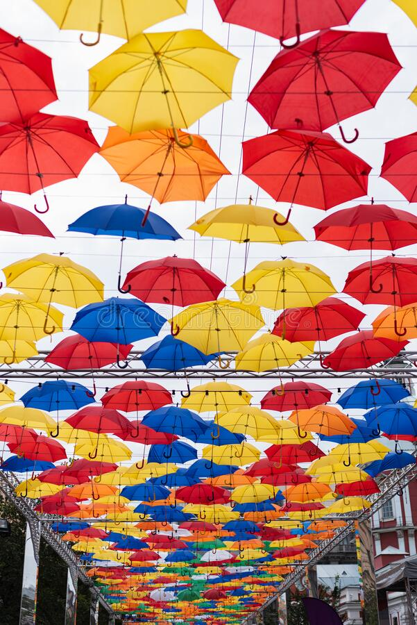 Many multi-colored umbrellas in the sky, unusual summer street scenery. Multi-colored umbrellas in the sky, unusual summer street scenery royalty free stock photos