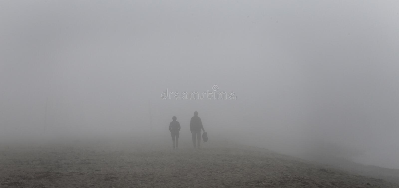 People walking on the beach under a heavy midday Fog covering el arenal beach in mallorca. Rare and unusual heavy fog over the coast with sun umbrellas and royalty free stock image