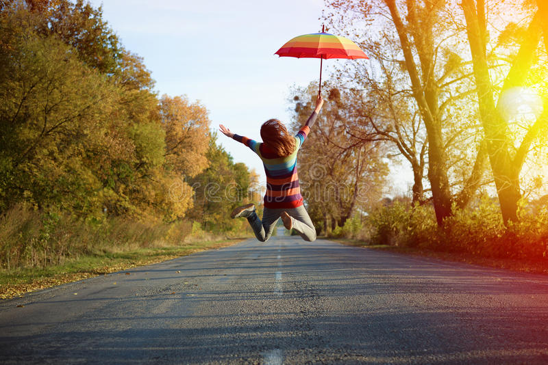 Picture of jumping lady holding umbrella with arms. Conceptual picture of jumping lady holding umbrella with arms sideways on empty country road in autumn stock photo