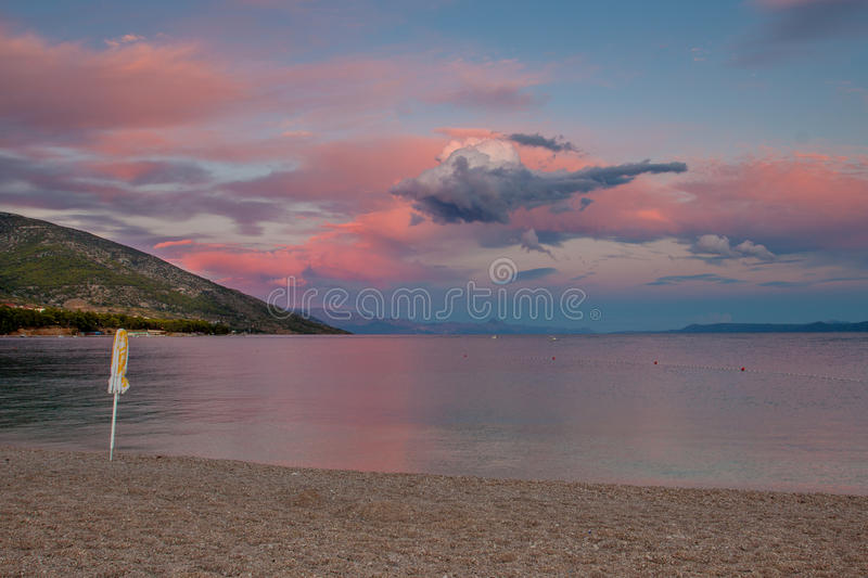 Stunning sunset on the sea. Pink, blue and white clouds with unusual shapes at sunset. On the pebbly beach is closed in the sun umbrella, the sea and a small stock image