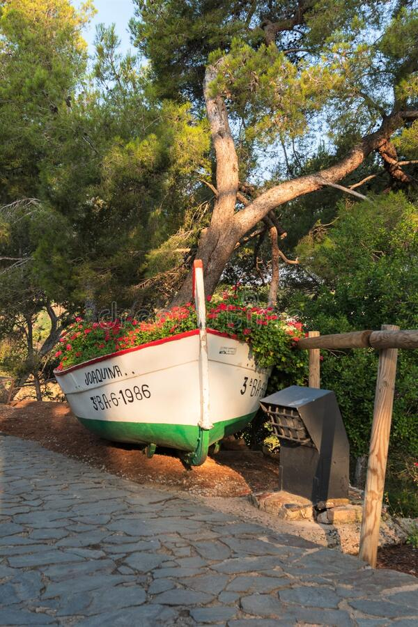 Tossa de Mar, Spain, August 2018. A boat used as a flowerbed in an old park. The original use of a vintage boat as an art object that draws attention to the stock photography