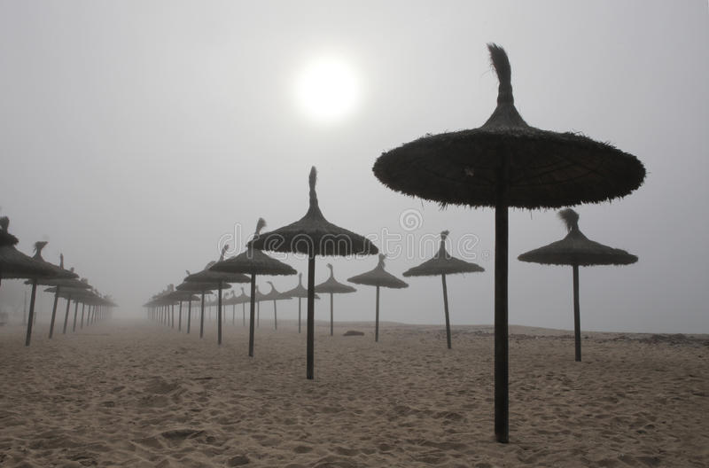 Unusual Fog in el arenal beach in mallorca. Rare and unusual heavy fog over the coast with sun umbrellas of El Arenal beach touristic area during winter in the stock photo