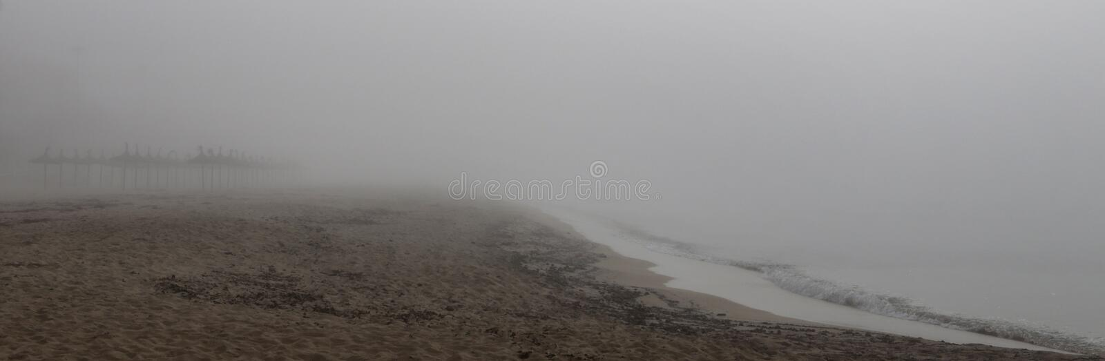 Unusual Fog in el arenal beach in mallorca wide. Rare and unusual heavy fog over the coast with sun umbrellas and shoreline of El Arenal beach touristic area royalty free stock photos