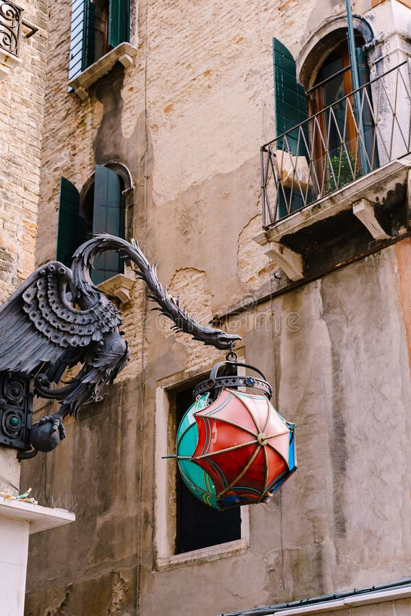 An unusual street lamp in the shape of The Maforio Dragon on the corner of the building, with a ball of three umbrellas. Blue, green and red, on the streets royalty free stock image