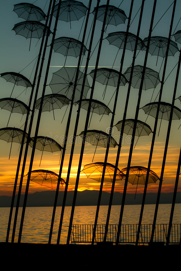 Unusual umbrella sculptures. Unusual umbrellas by sea with golden sunset in background, Thessaloniki, Greece royalty free stock photography