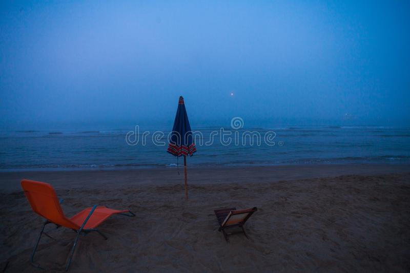 A view of an umbrella and two deckchairs on the beach during an unusual summer foggy morning.  stock photos