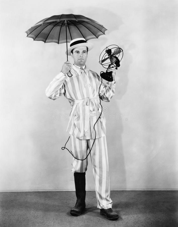 The weather man with umbrella, boot and fan. (All persons depicted are no longer living and no estate exists. Supplier grants that there will be no model royalty free stock photos