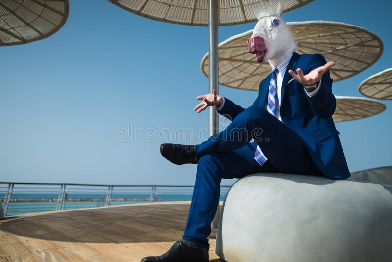 Young businessman in suit sits under umbrellas on the city waterfront. And spreads his hands. Unusual man in funny mask gesticulate on city promenade. Elegant stock images