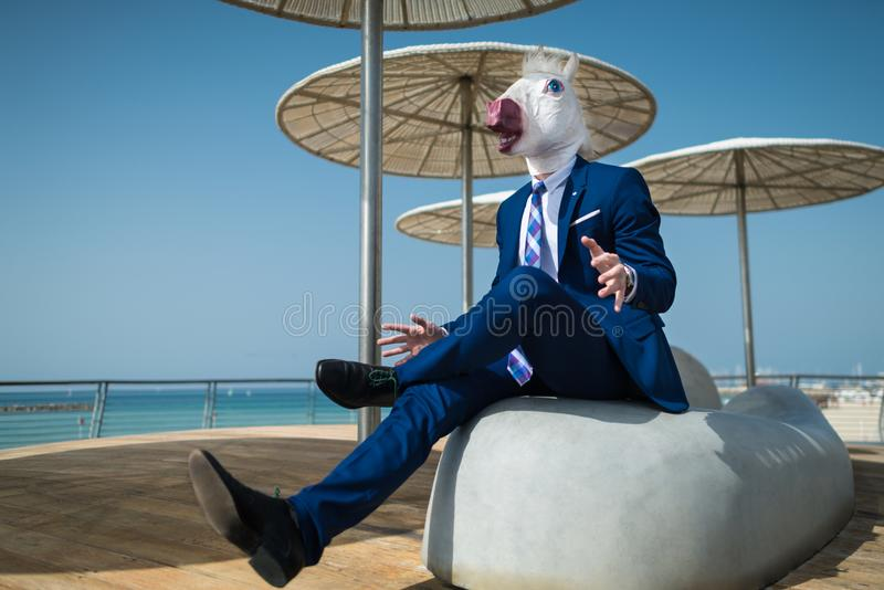 Young manager in suit under umbrellas and spreads his hands. On the city waterfront. Unusual manager in comical mask is surprised. Funny unicorn sits at city royalty free stock photography
